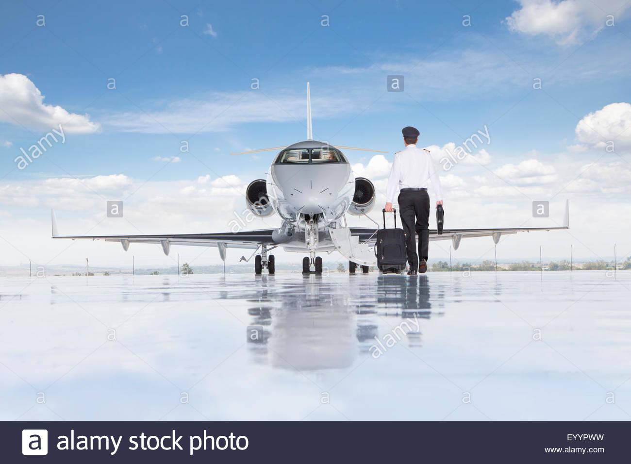 Pilot walking towards private jet - Stock Image