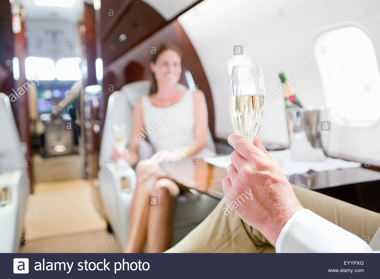 Close-up of glass of champagne in man's hand with woman in background on private jet - Stock Image