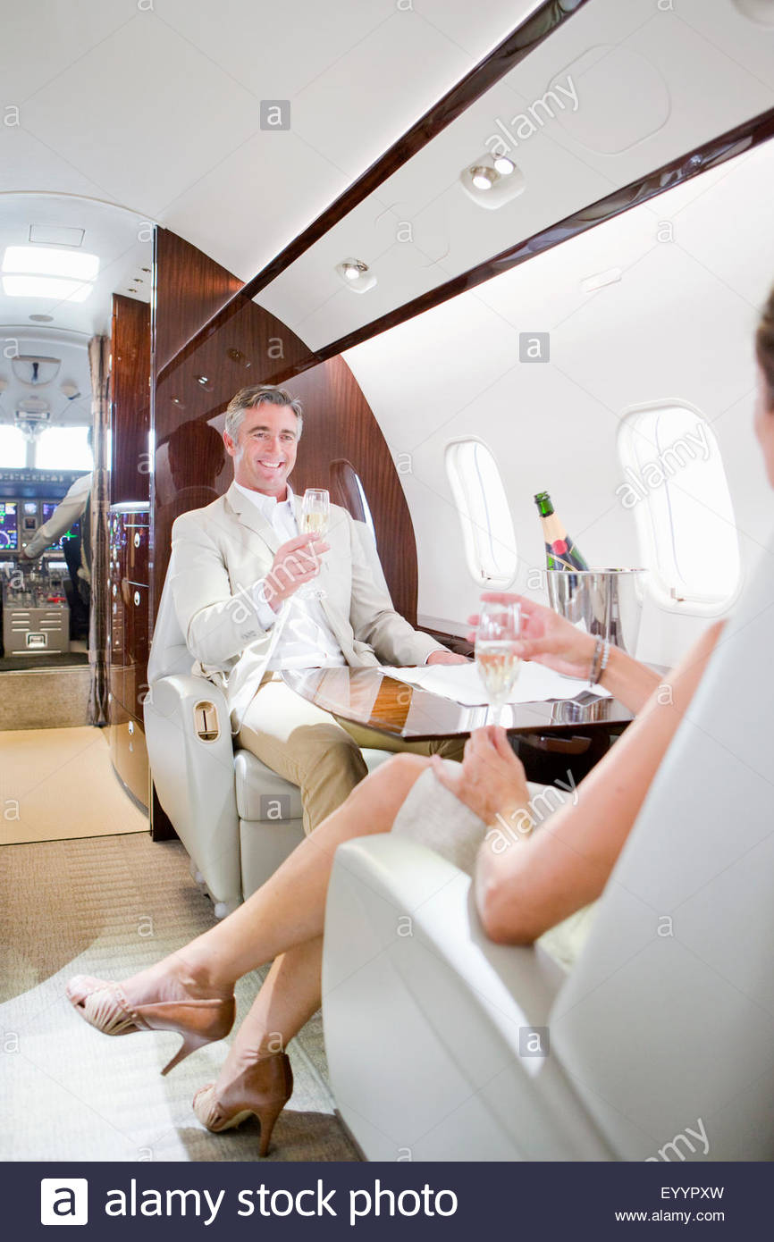 Attractive smiling couple drinking champagne on private jet - Stock Image