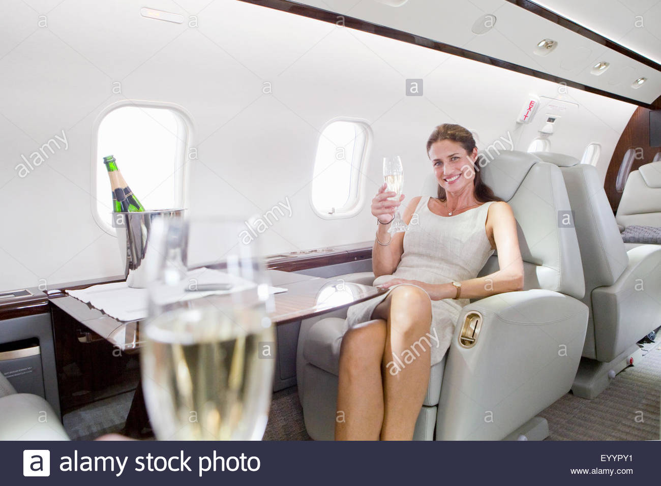 Luxury Woman On Airplane : Attractive woman sitting and holding champagne glass in