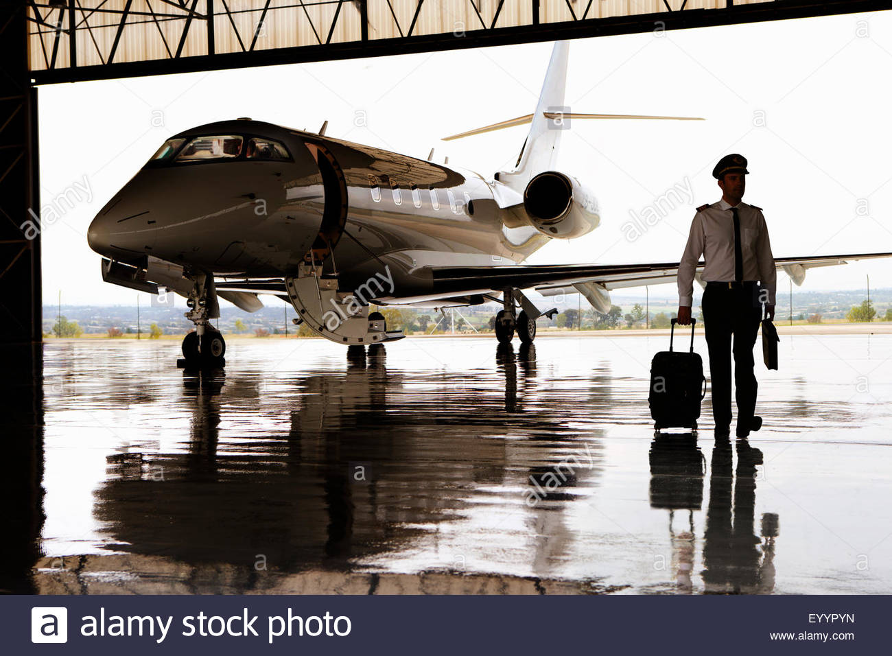 Silhouette of pilot walking away from private jet in hangar - Stock Image