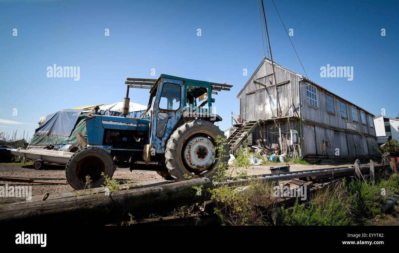Old tractor and old supplies shed at Tollesbury Saltings on the Essex Coast Stock Photo