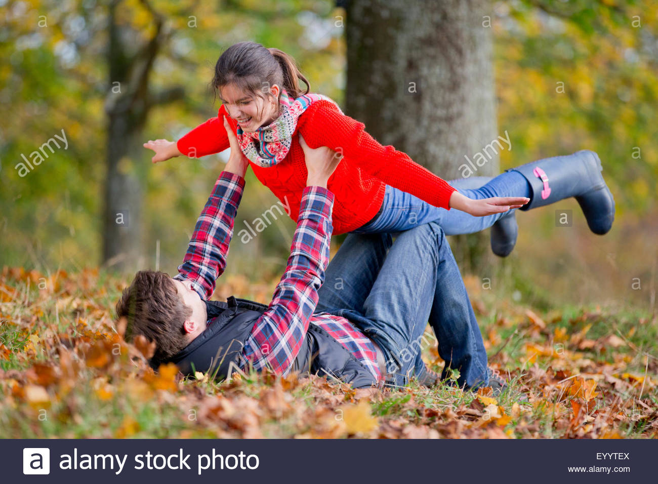 Father holding daughter up like a plane in autumnal park - Stock Image