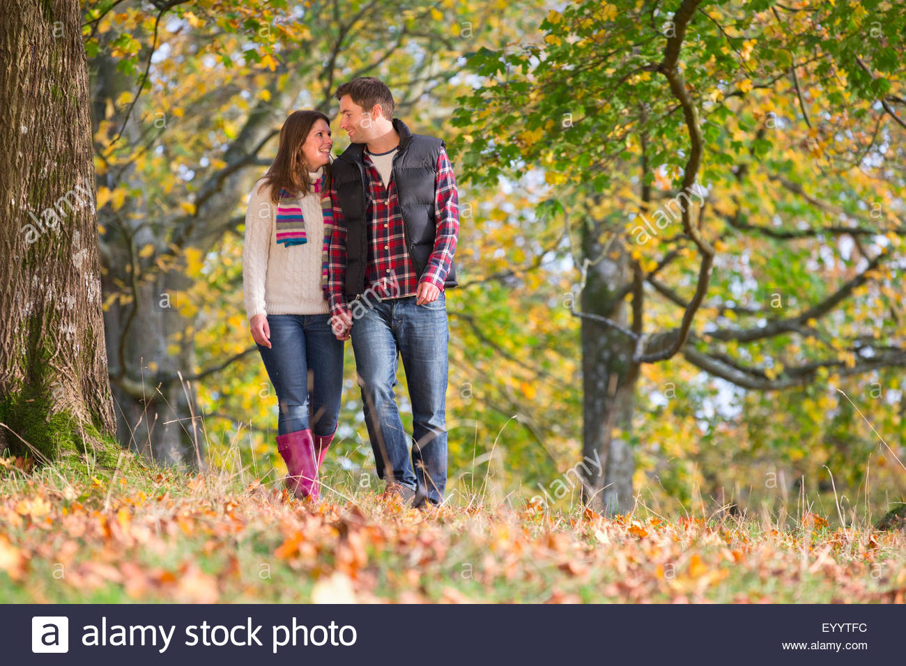 Happy couple, walking through autumnal forest, holding hands Stock Photo