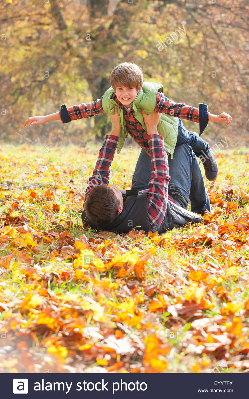 Father holding son up like a plane in autumnal park - Stock Image