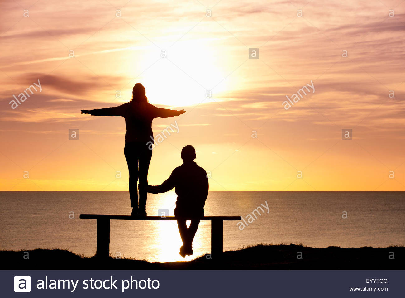 Silhouette of couple, standing on bench with arms outstretched, against sunset over the ocean - Stock Image