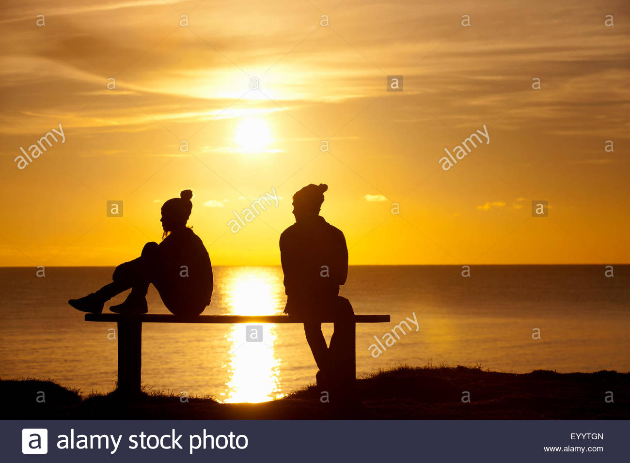 Silhouette of couple, sitting separately on bench, against sunset over the ocean - Stock Image