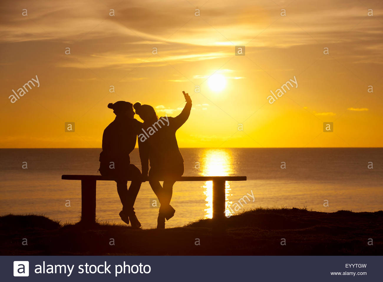 Silhouette of couple, sitting on bench taking selfie on mobile phone, against sunset over the ocean Stock Photo