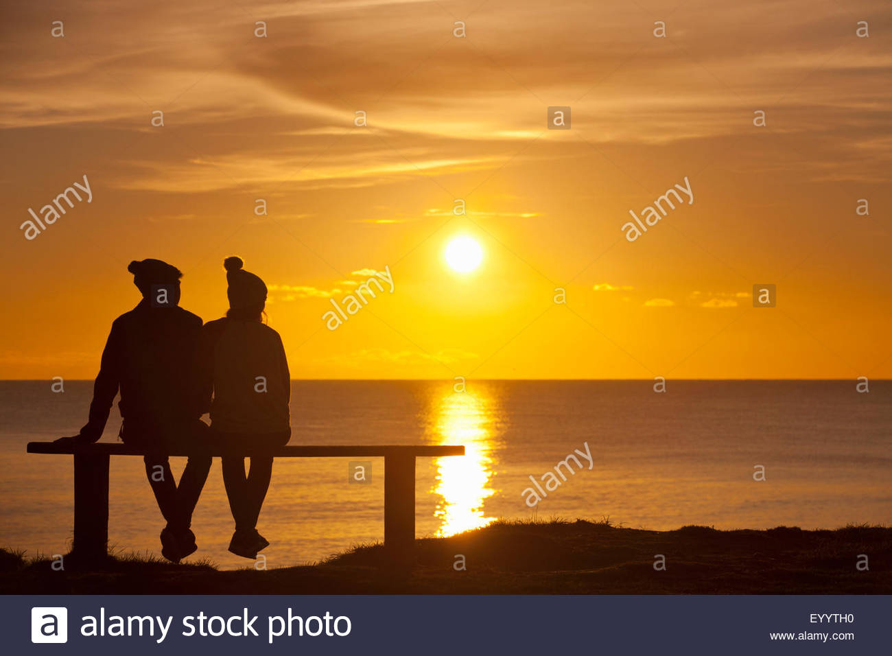 Silhouette of couple, sitting on bench, against sunset over the ocean - Stock Image