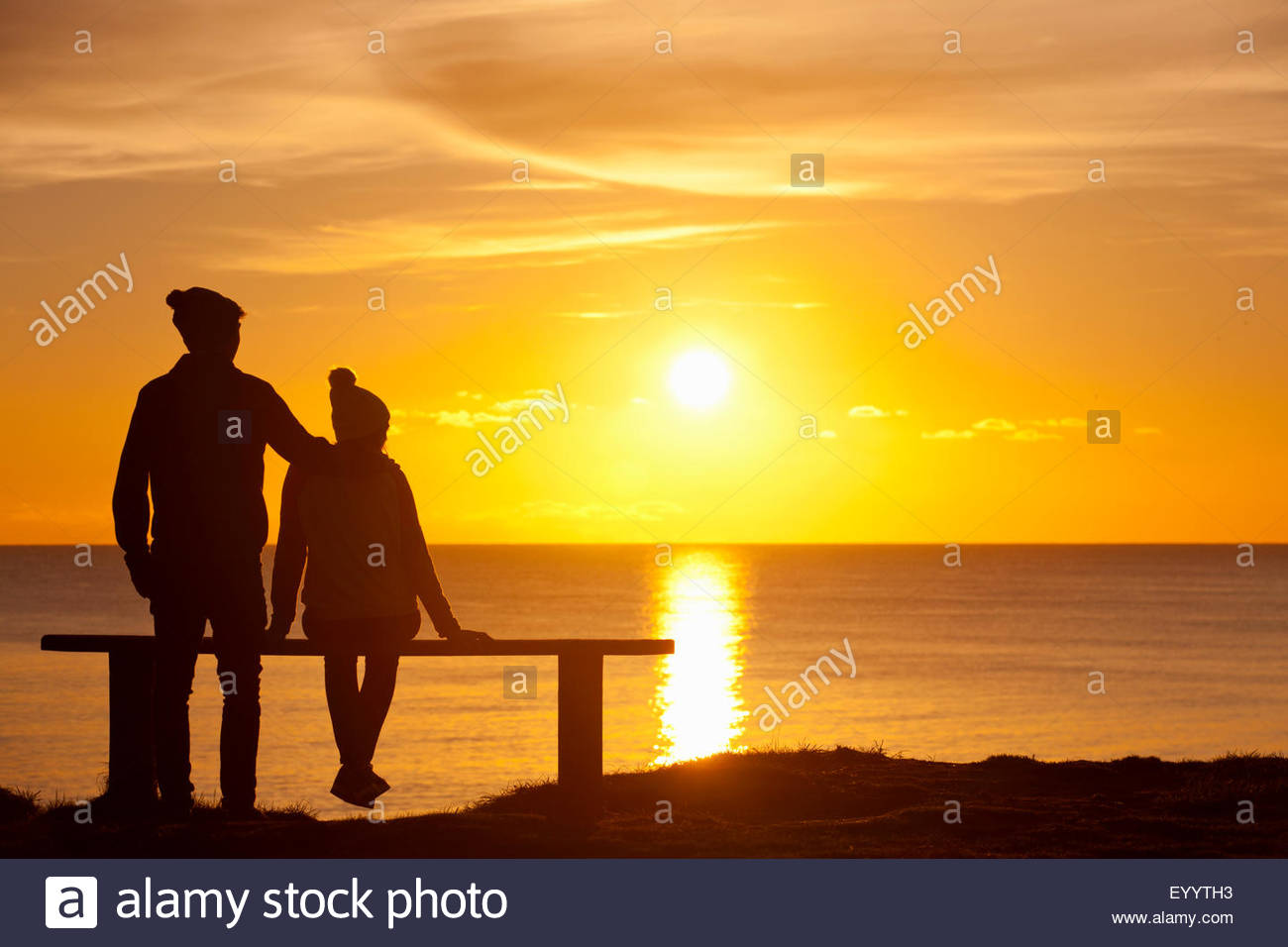 Silhouette of couple, on bench, against sunset over the ocean - Stock Image