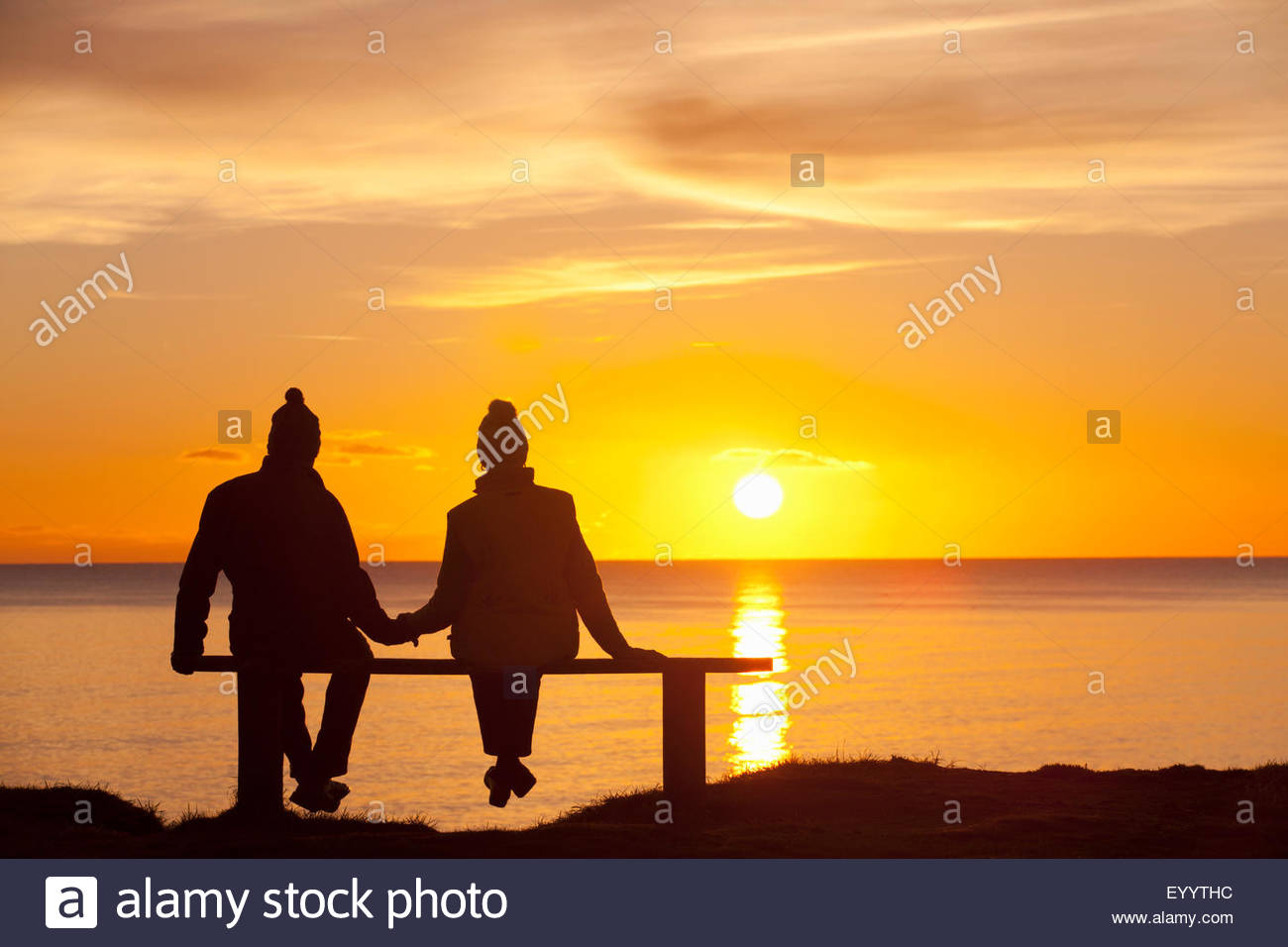 Silhouette of couple, sitting on bench, holding hands, against sunset over the ocean - Stock Image