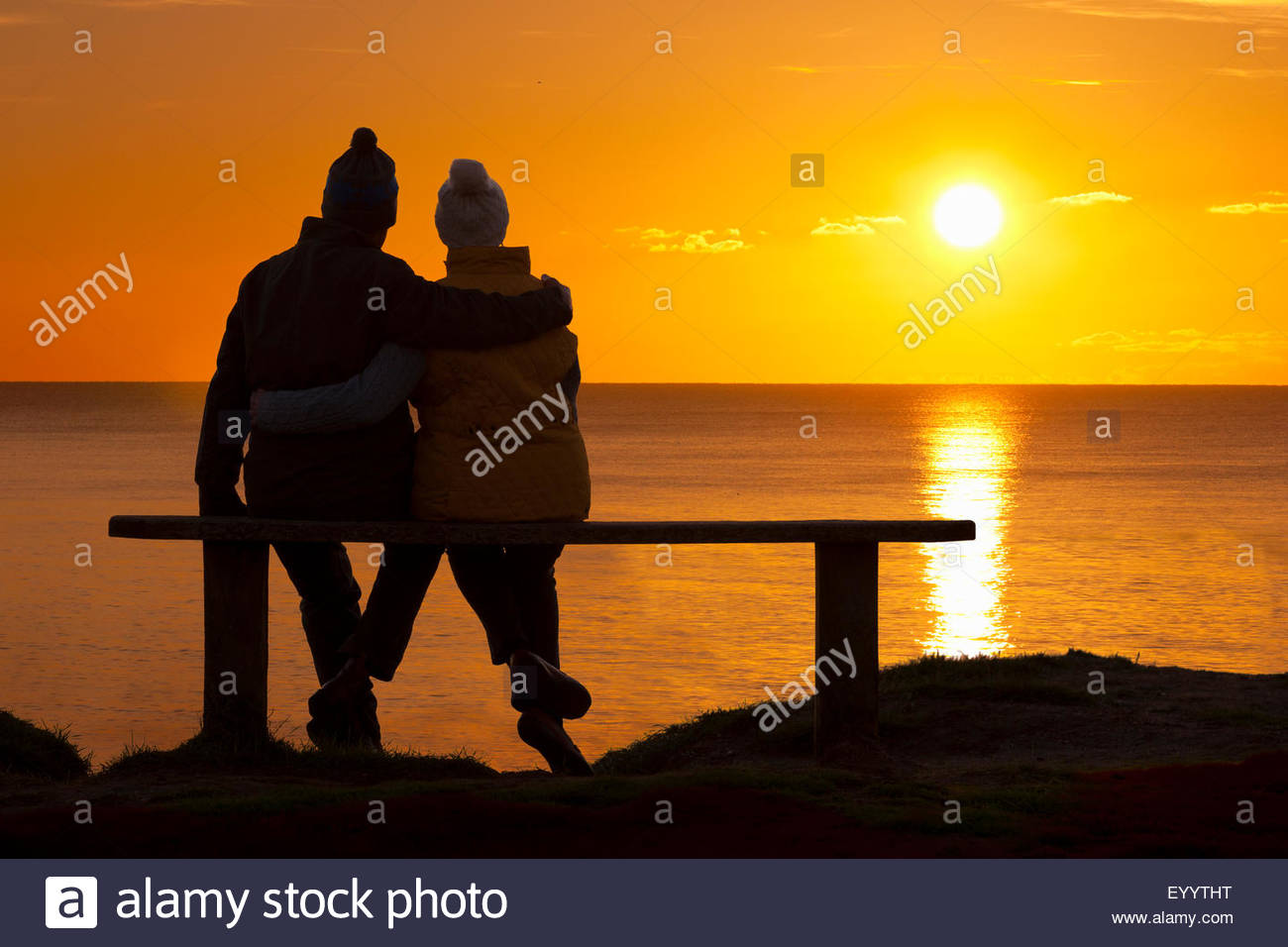 Silhouette of couple, sitting on bench with arms round each other, against sunset over the ocean - Stock Image