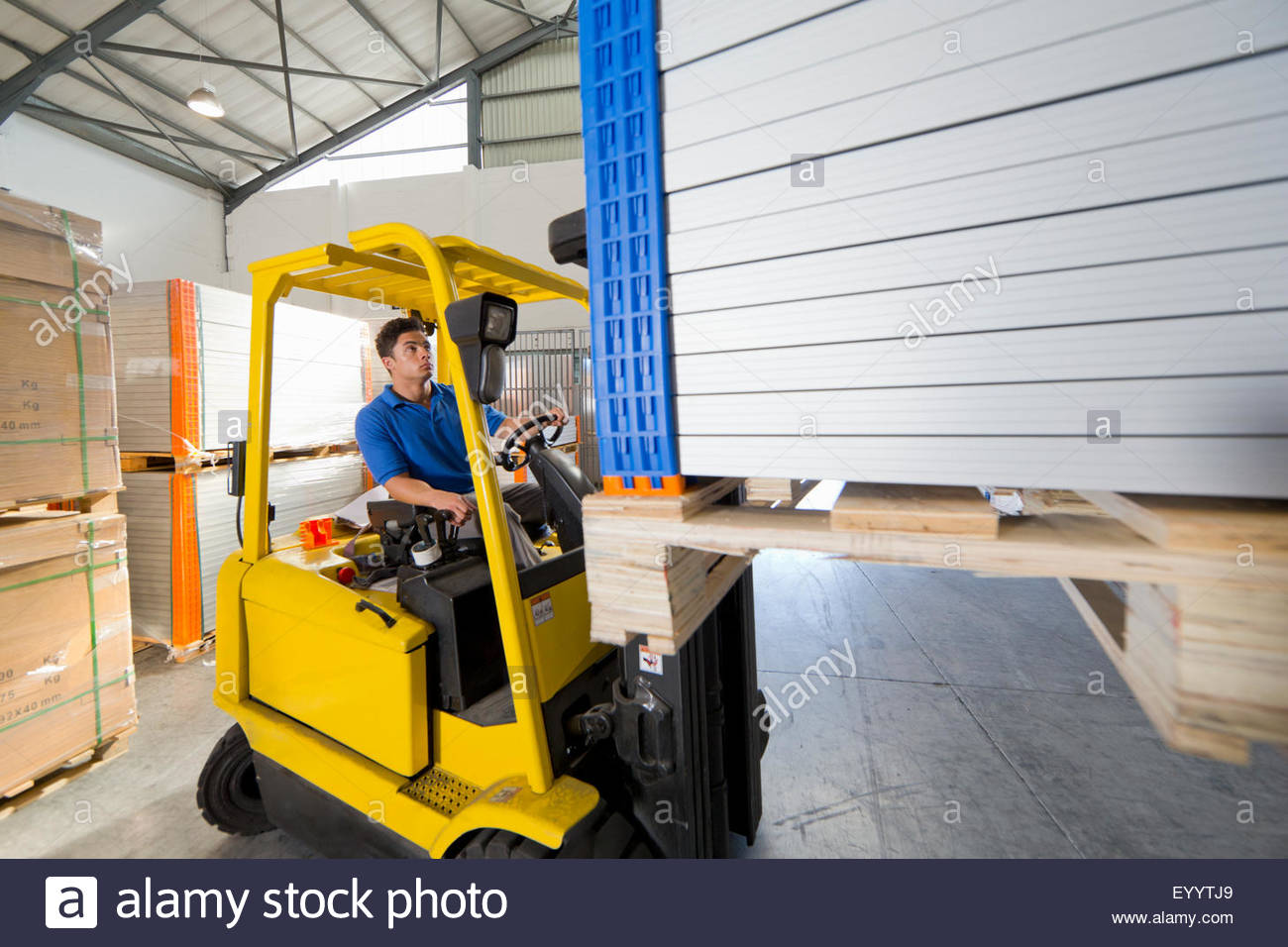 Forklift truck driver worker stacking panels in solar panel factory warehouse - Stock Image
