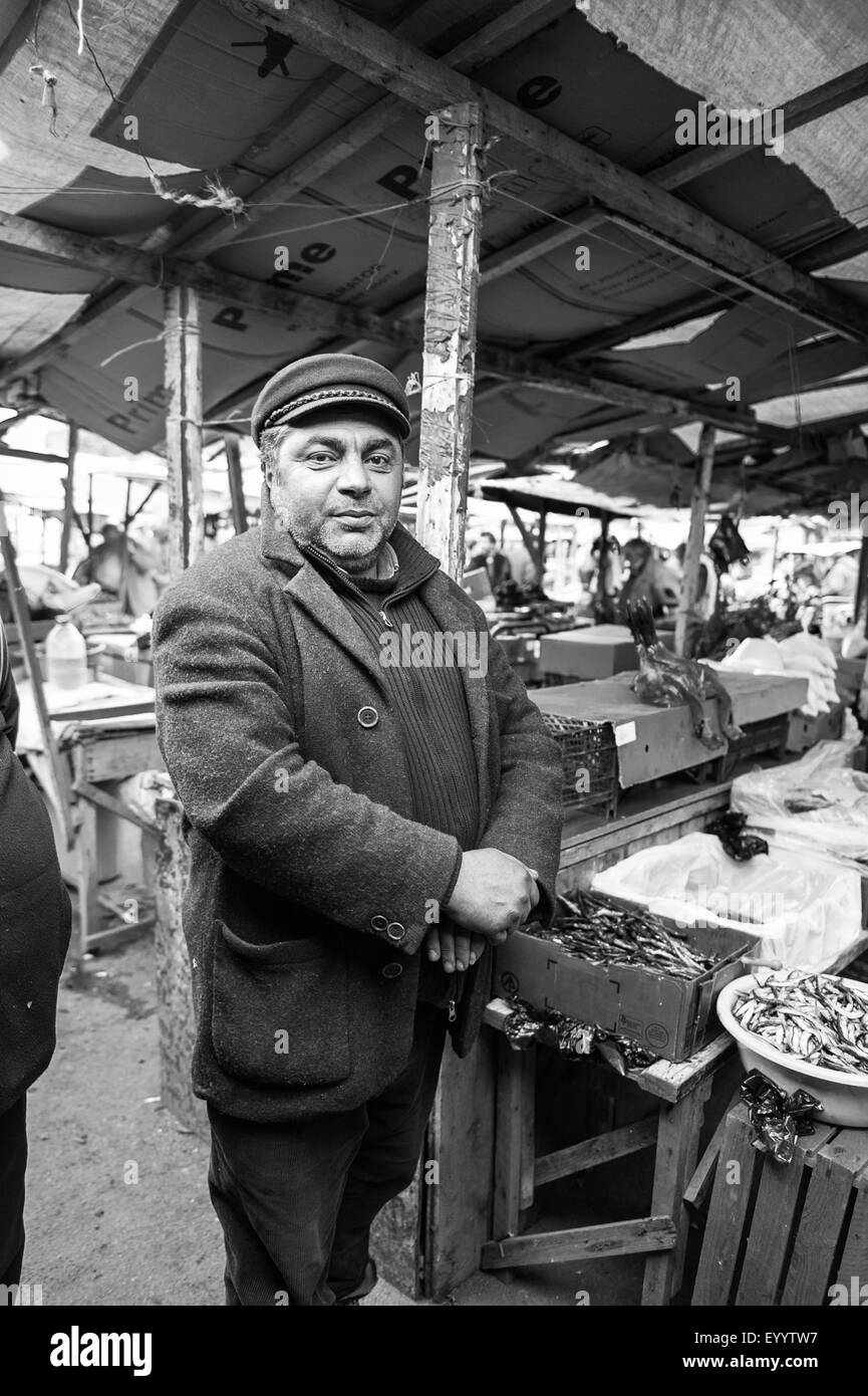 Scenes taken from an outdoor market in Gori, Georgia, Asia. A market trader stands next to his fish stall. - Stock Image