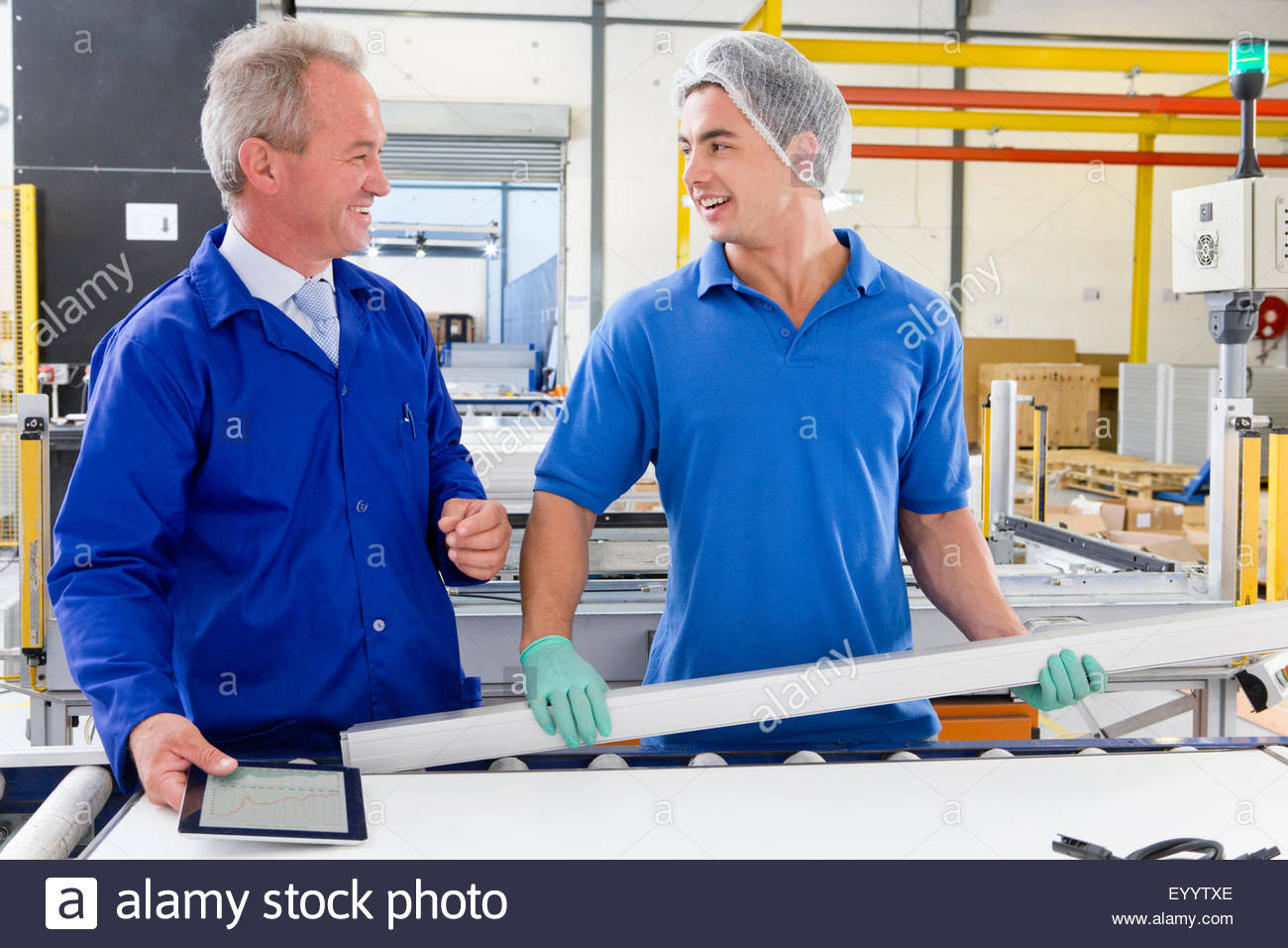 Supervisor training worker apprentice on solar panel factory floor production line - Stock Image