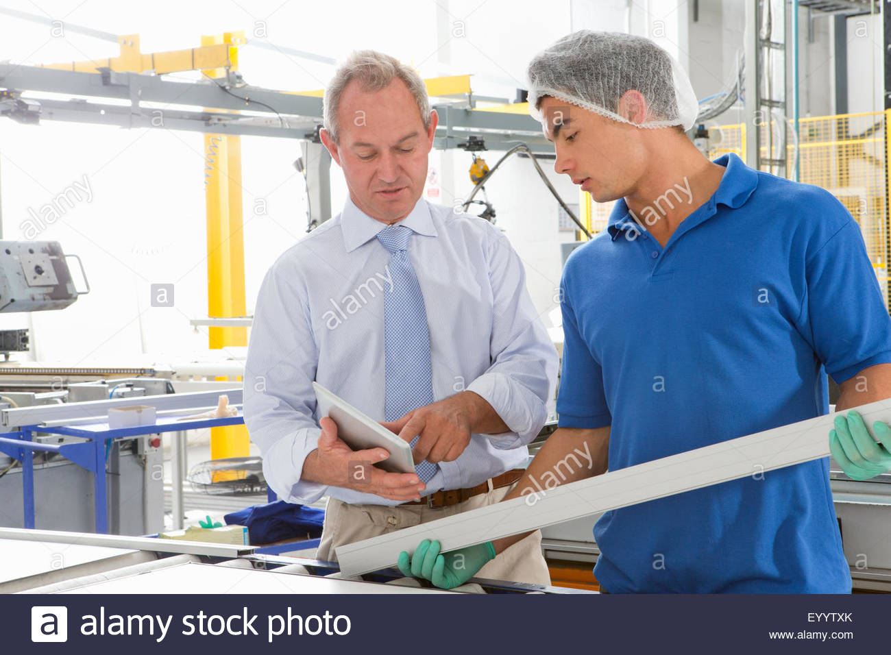 Supervisor training worker apprentice with digital tablet on solar panel factory floor production line - Stock Image