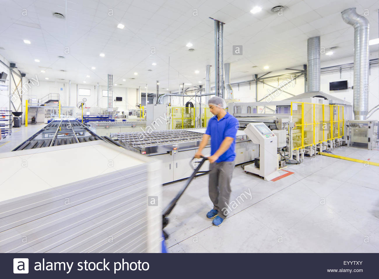 Worker pulling pallet of solar panels on factory floor - Stock Image