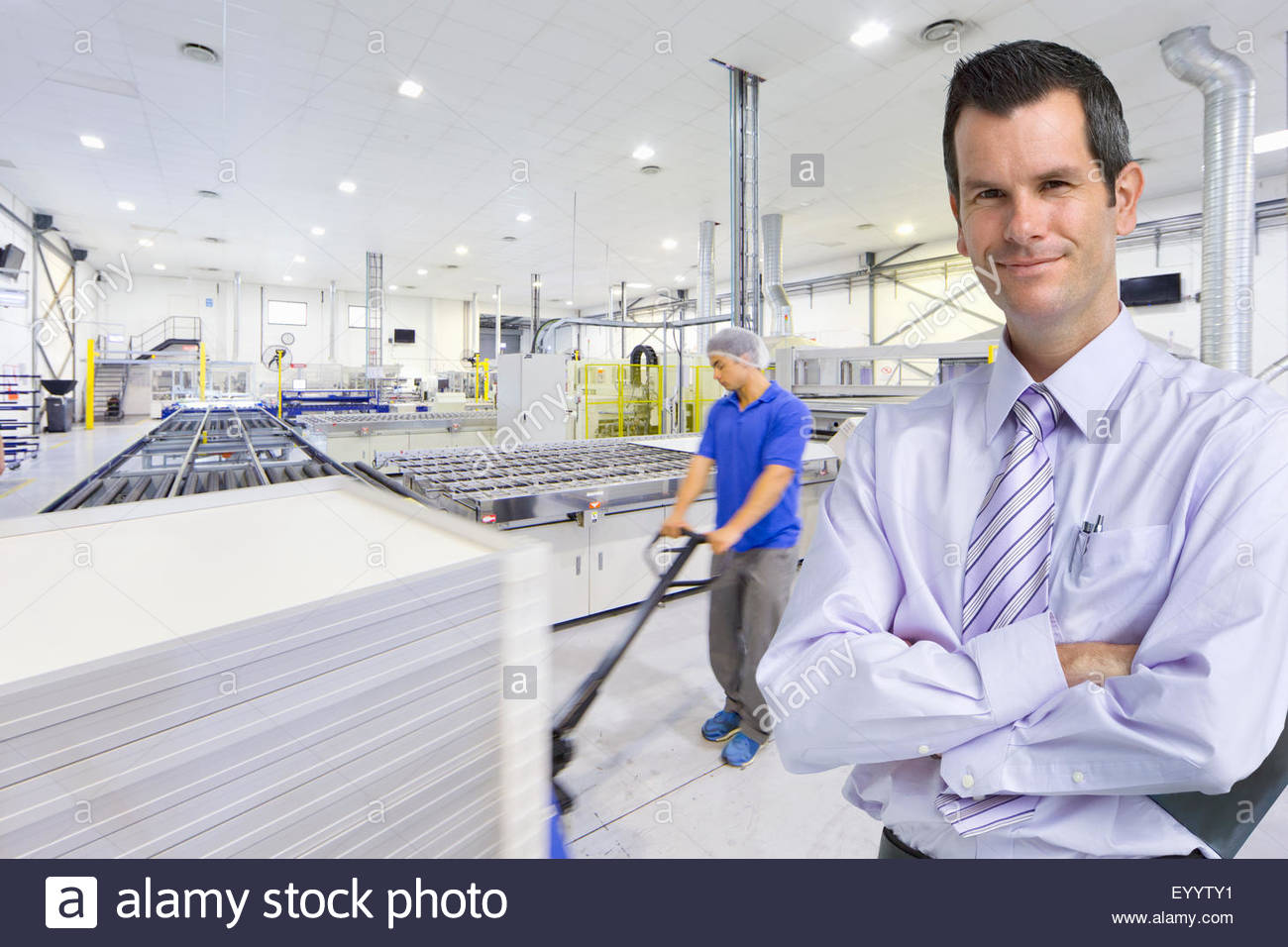 Portrait of businessman owner smiling at camera with worker pulling pallet of solar panels in factory - Stock Image