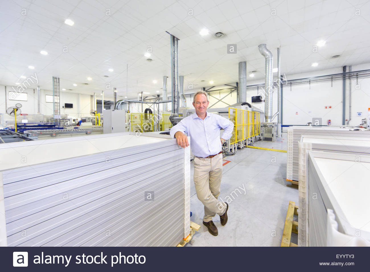 Portrait of businessman owner with solar panels on factory floor production line smiling at camera Stock Photo