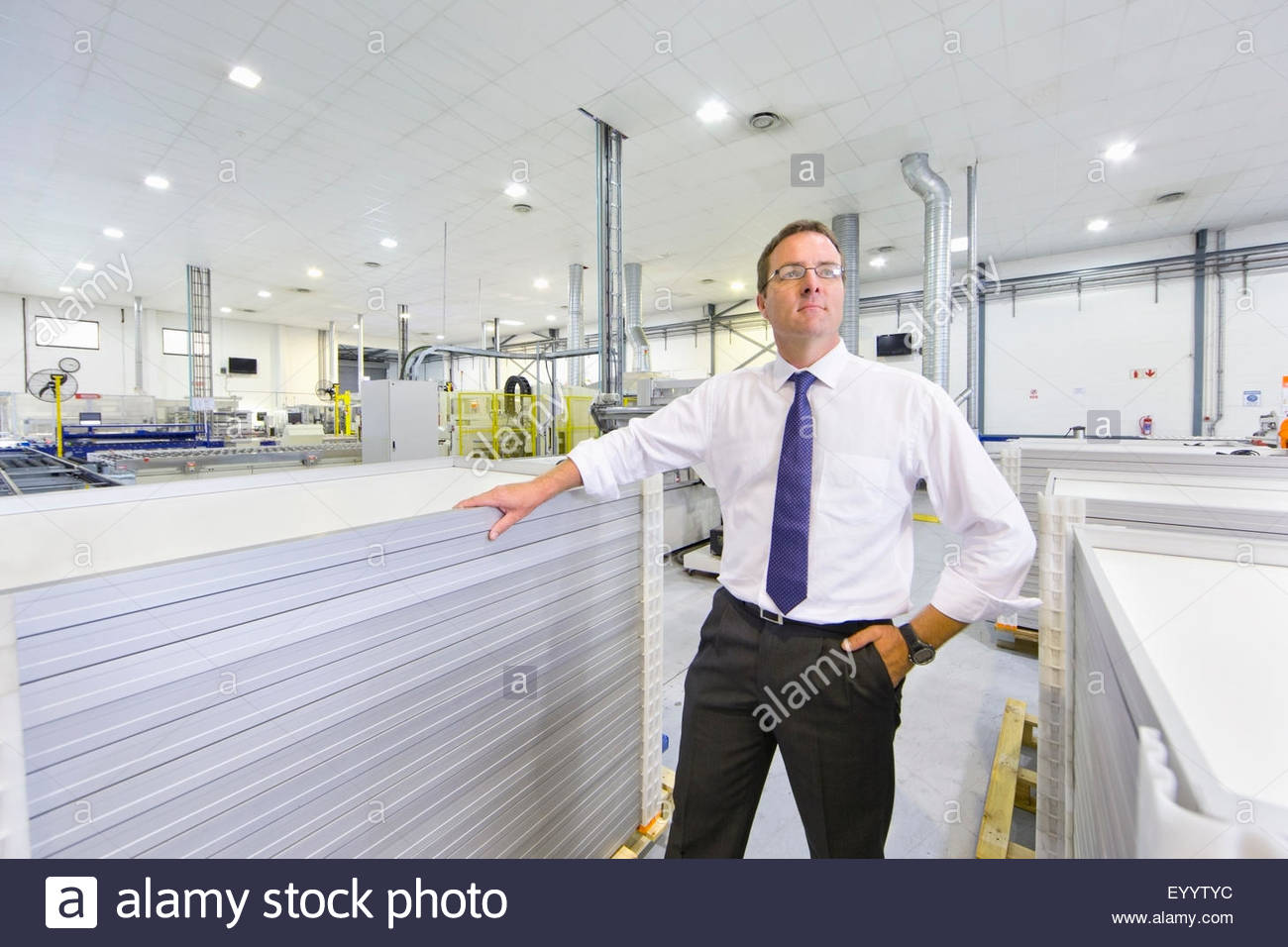 Portrait of businessman owner with solar panels on factory floor production line looking at camera - Stock Image