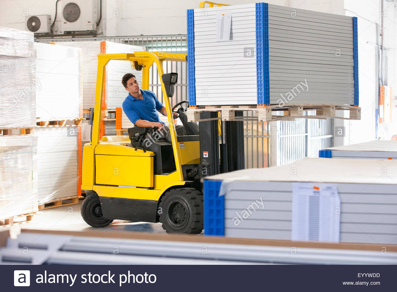 Forklift truck driver stacking solar panels in factory warehouse - Stock Image