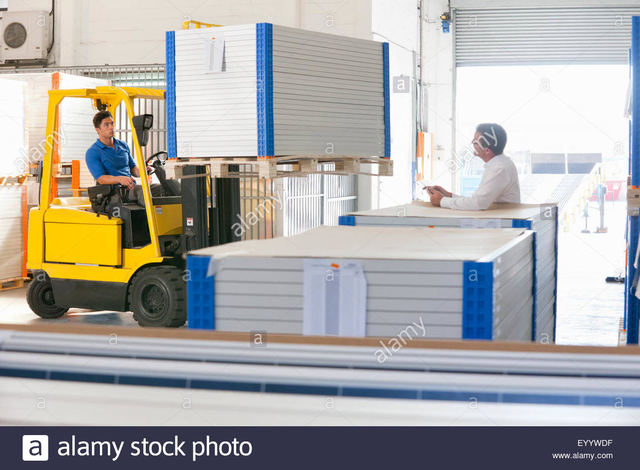 Businessman supervising forklift truck driver in solar panel factory warehouse - Stock Image
