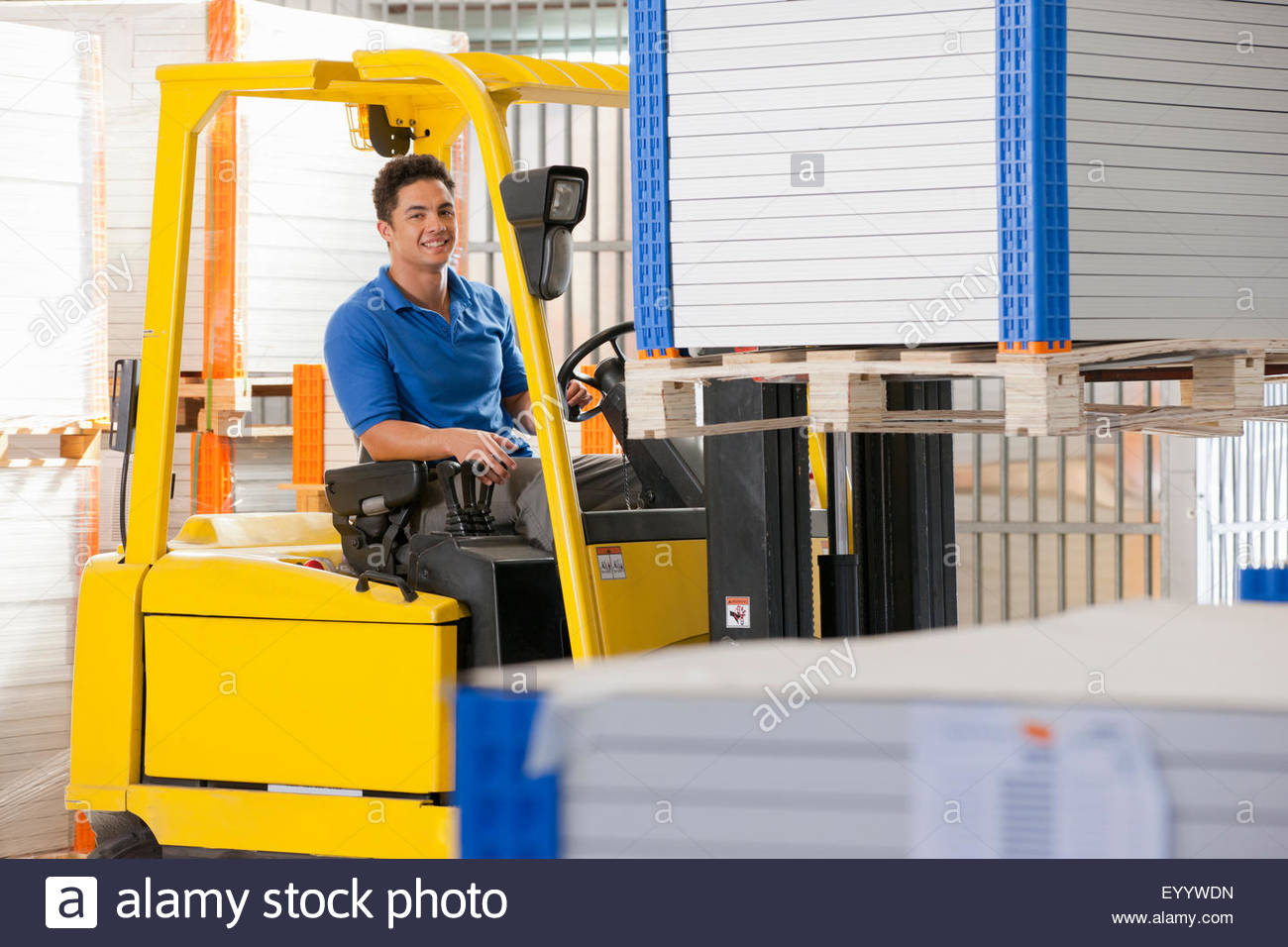 Forklift truck driver smiling at camera stacking solar panels in factory warehouse - Stock Image