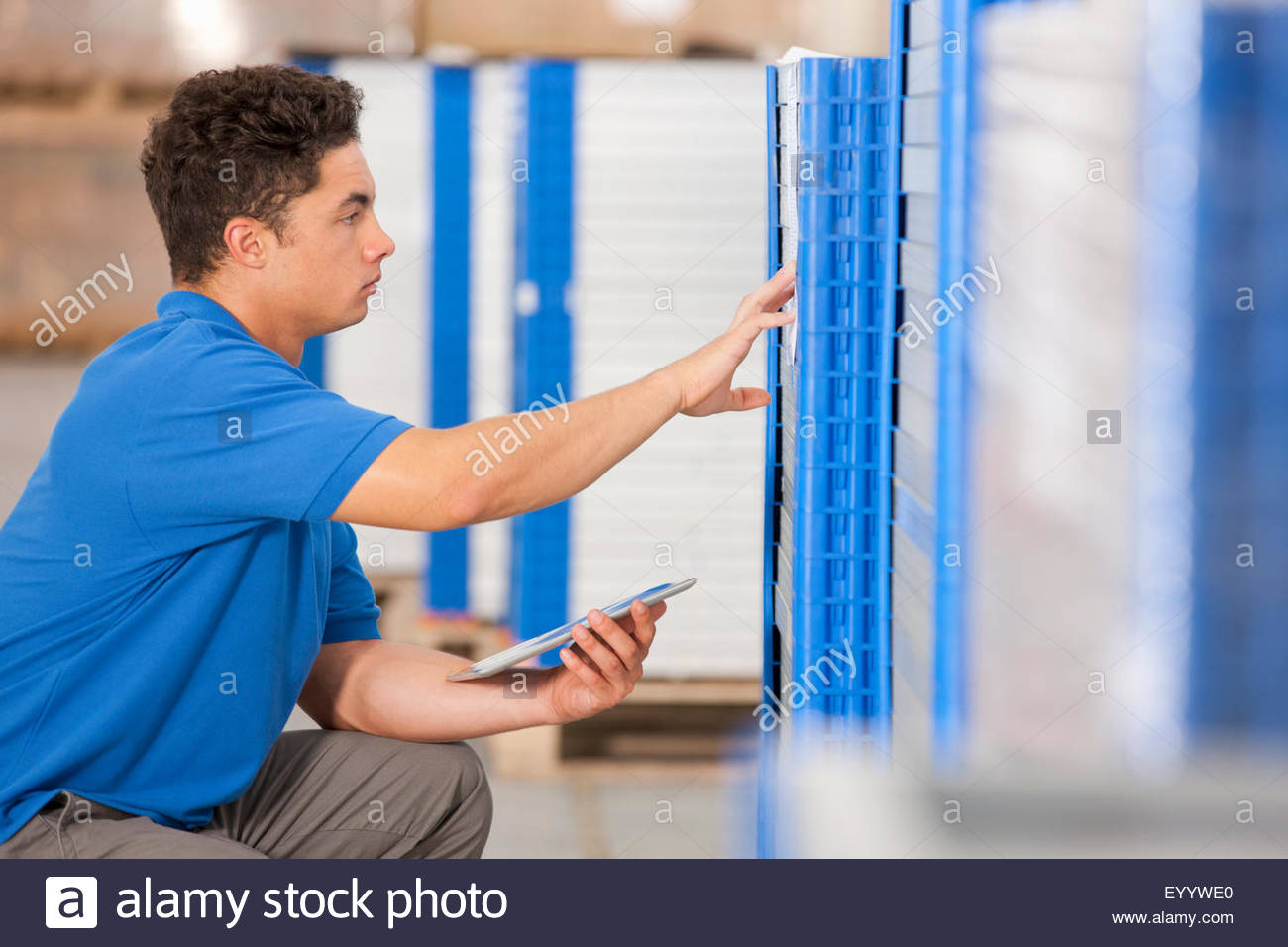 Warehouse worker checking solar panels with digital tablet - Stock Image