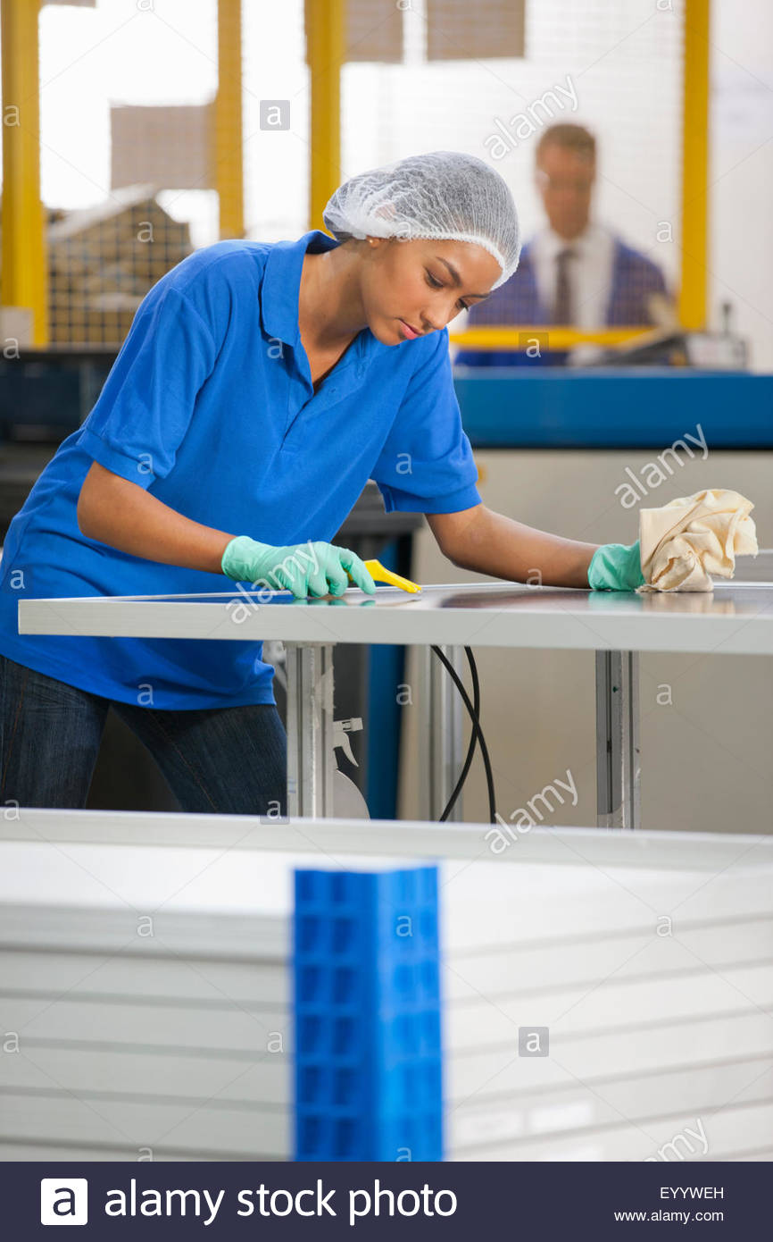 Technician worker cleaning and checking newly manufactured solar panels Stock Photo
