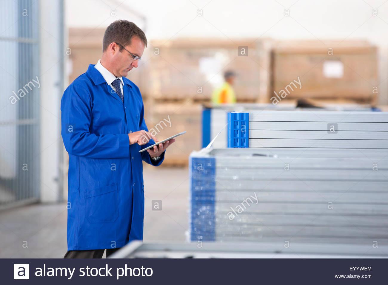 Supervisor worker stock checking solar panels in factory warehouse - Stock Image