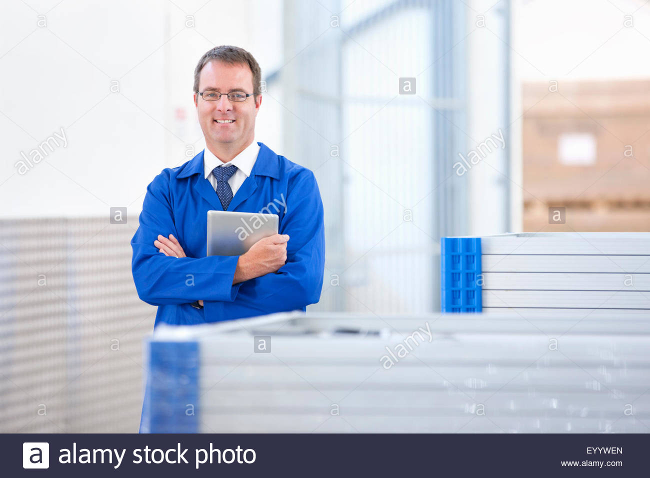 Supervisor worker smiling at camera stock checking solar panels in factory warehouse - Stock Image