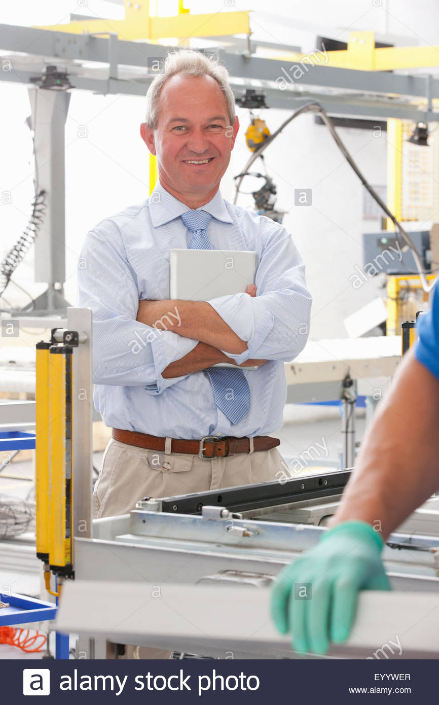 Businessman supervising worker and smiling at camera in solar panel factory production line - Stock Image
