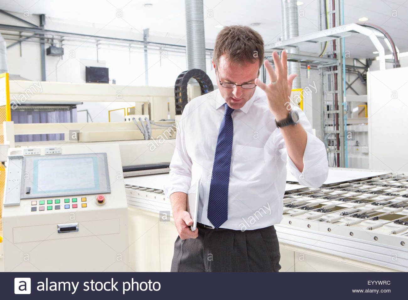 Frustrated Businessman in solar panel factory production line - Stock Image