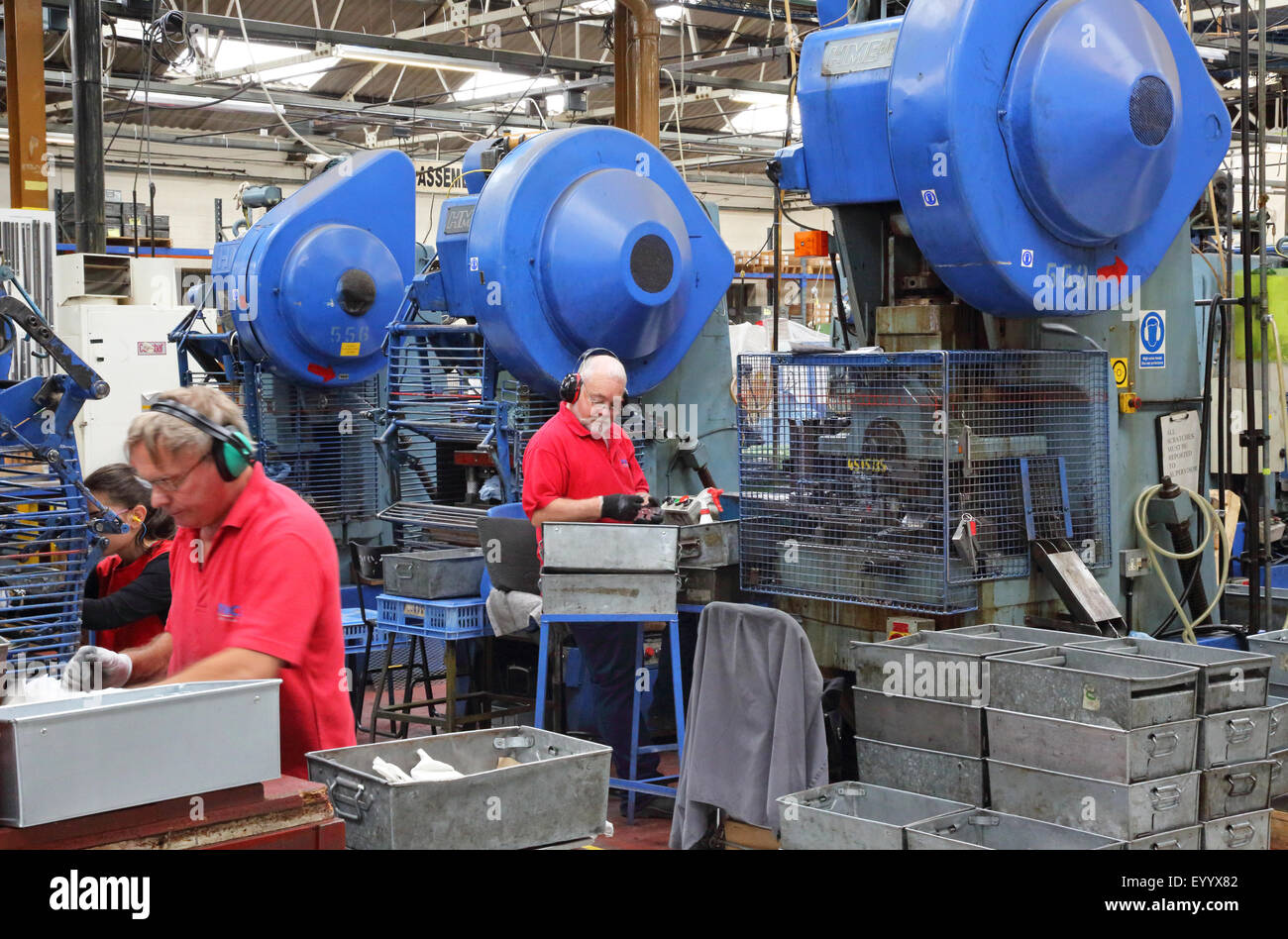 Workers in a factory manufacturing metal components for the construction industry using large steel pressing machines - Stock Image