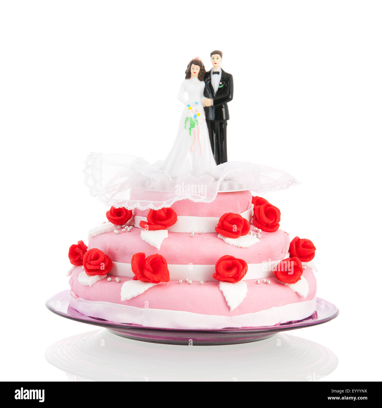 Pink wedding cake with red roses and couple on top Stock Photo ...
