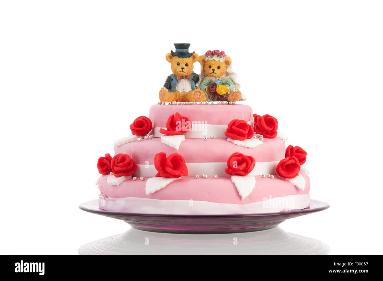 Pink wedding cake with red roses and bear bride and groom on top ...