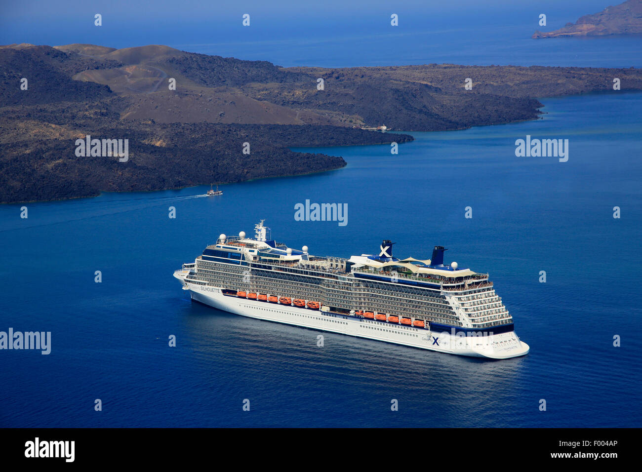 cruise liner in front of volcanic Island Nea Kameni, Greece, Cyclades, Santorini - Stock Image