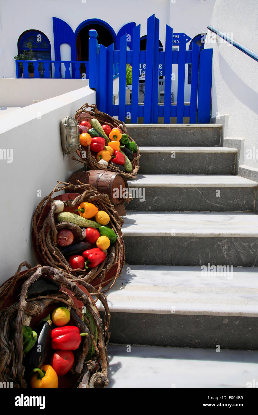 vegetable baskets on a white stair, blue gate, Greece, Cyclades, Santorin - Stock Image