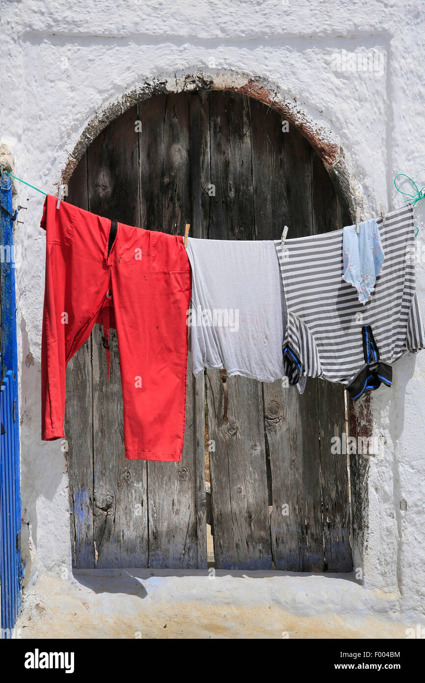 coloured washing hanging on a clothesline in front of an old wooden door, Greece, Cyclades, Santorin - Stock Image
