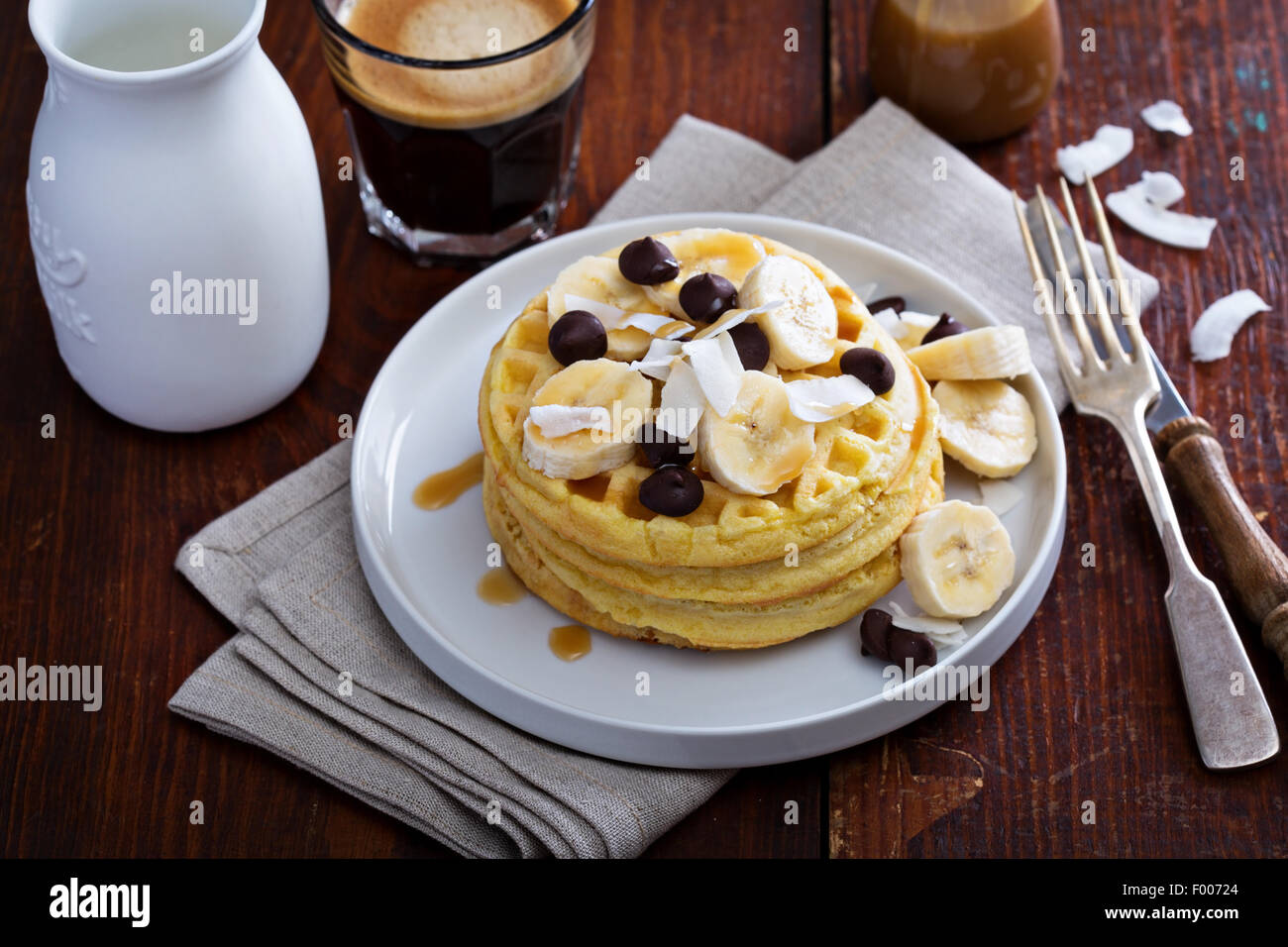 Waffles with banana slices, caramel and chocolate - Stock Image