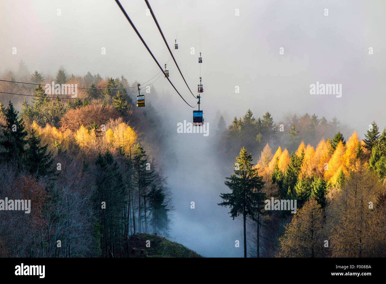 cable way comes from the sunshine on summit to the mist in the valley, Germany, Bavaria, Kampenwand, Hohenaschau - Stock Image
