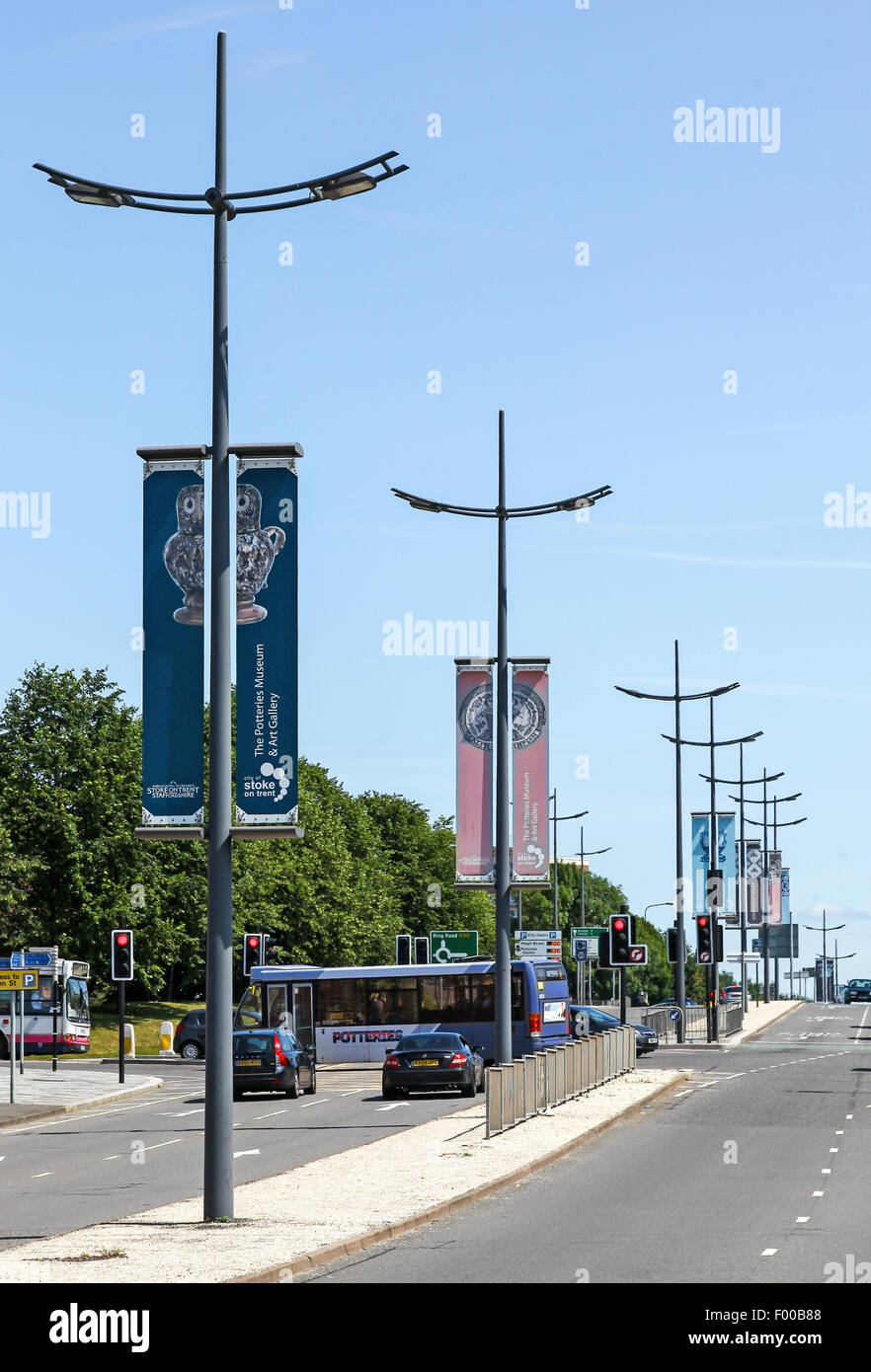 Banners on lamp posts on a road in Stoke on Trent displaying local pottery firms and the Hanley Museum - Stock Image