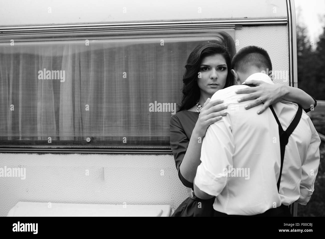 man and woman is hidden from view behind a trailer - Stock Image