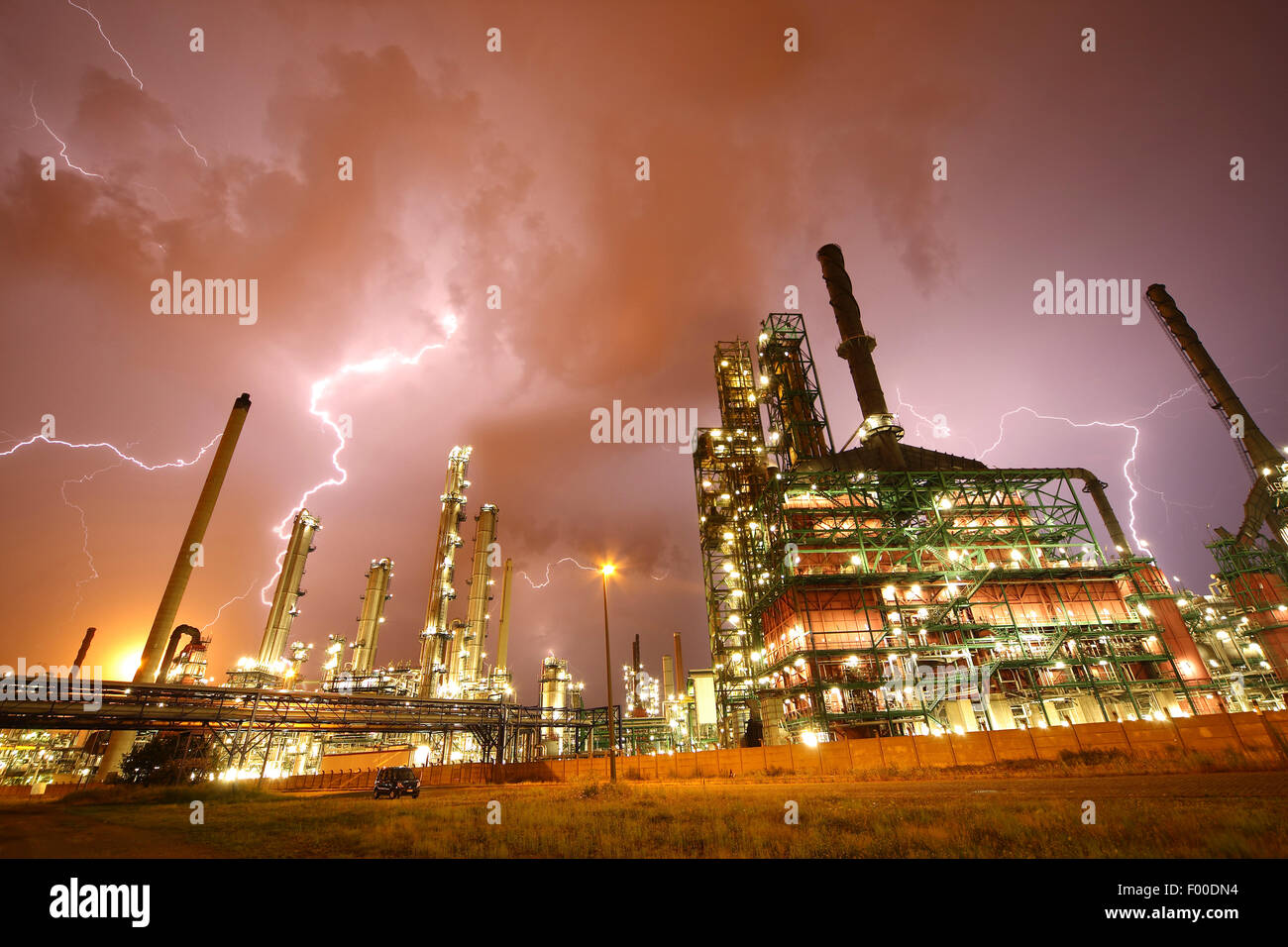 thunderstorm and lightning crashes above lightened petrochemical industry in Antwerp harbour at night, Belgium, - Stock Image