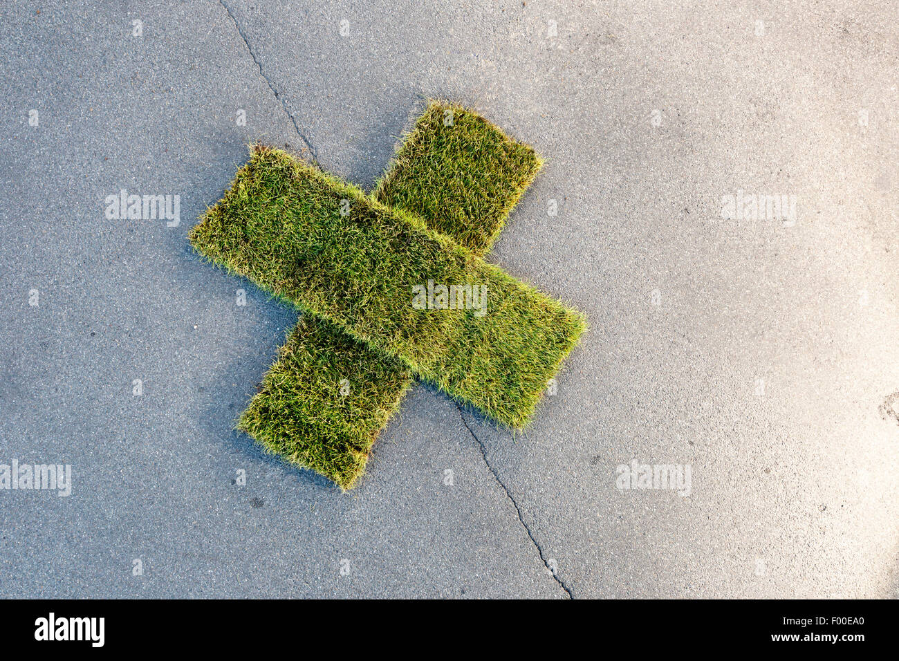 patch cross made of rolled sod on tarmac Stock Photo