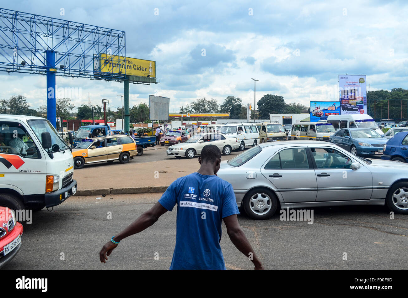 Man about to walk across a jammed roundabout in the city of Kumasi, Ghana (Suame circle) - Stock Image