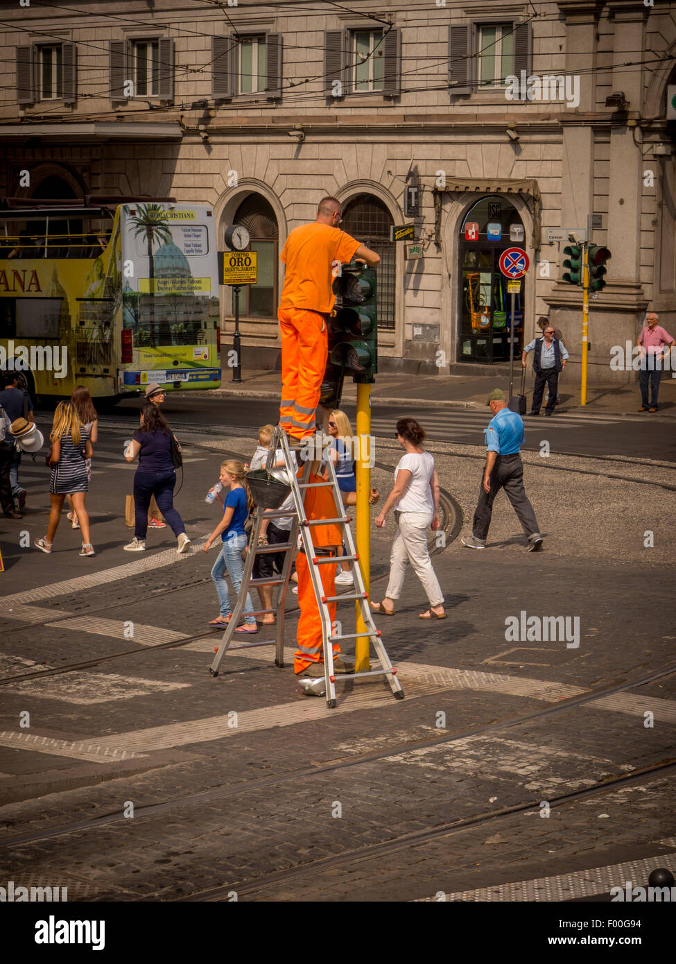 Workmen wearing high visibility orange clothes fixing traffic lights in the middle of a busy road in Rome. Italy. - Stock Image