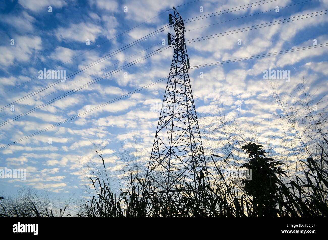 Electric pylon at sunset in rural Africa (Ghana) against a background of clouds - Stock Image