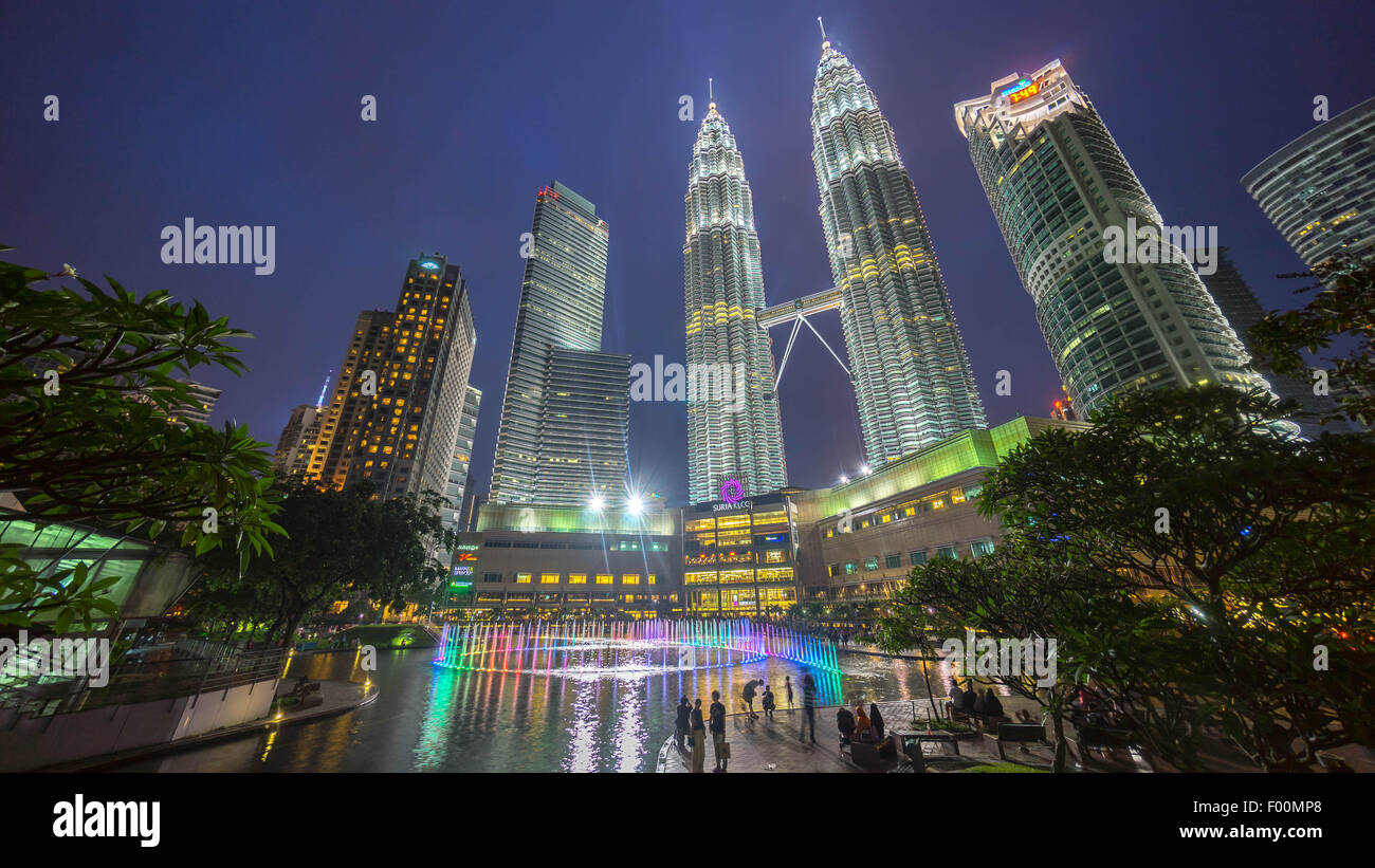 Water Fountain at Suria KLCC with Petronas Towers and Office Buildings at Blue Hour sunset at Night. - Stock Image
