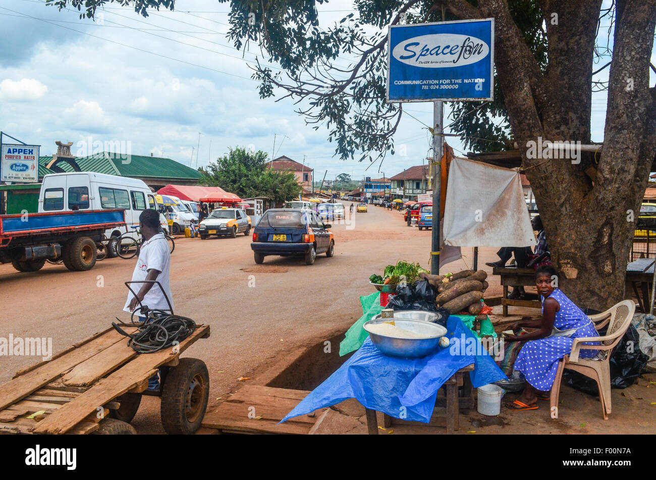 Rural scene in Ghana, town of Kade: woman selling vegetables by the main road - Stock Image
